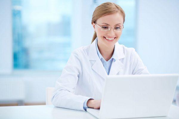 Врач стоматолог смотрит сайт стоматология на ноутбук